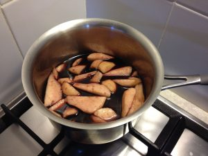 Fresh pears added to pears in red wine syrup