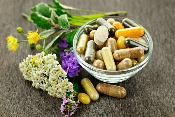 Bowl of supplements alongside fresh herbs