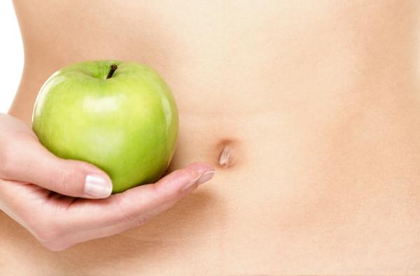 Picture of a woman holding a green apple next to her belly button
