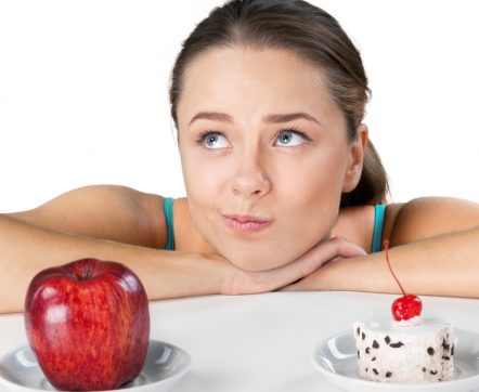 Woman deciding to eat either an apple or cake