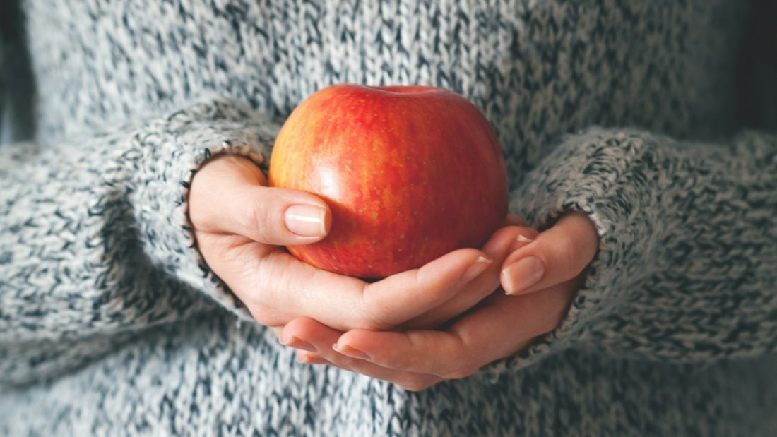 Woman holding a red apple in her hands