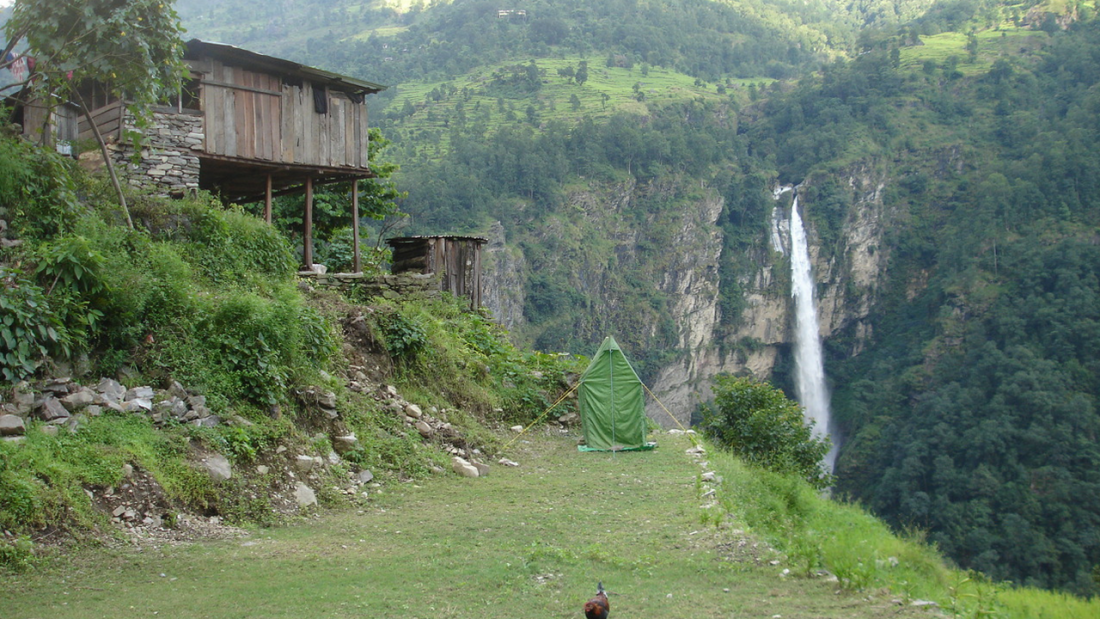 Camp ground at Soti Khola with waterfall and wooden houses