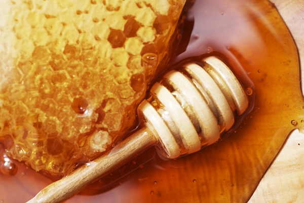 Honey alongside a piece of honeycomb