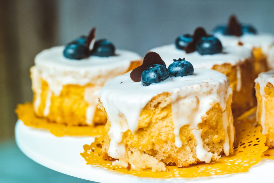 Lemon cake topped with icing and blueberries