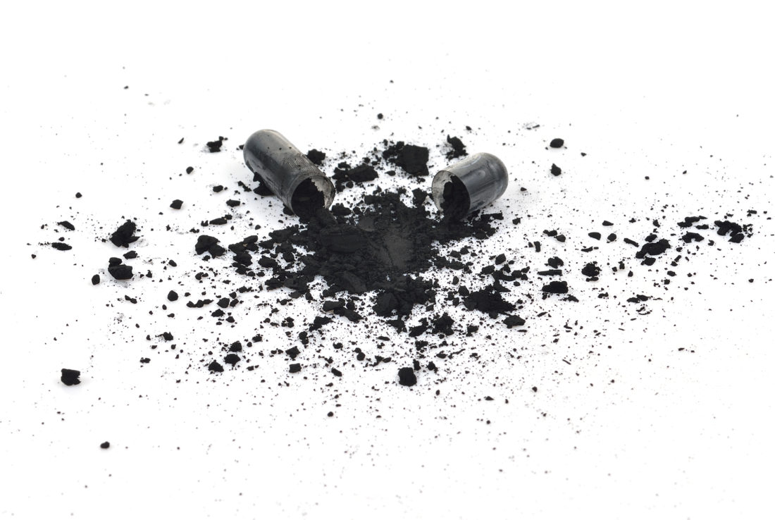 Capsule of activated charcoal opened onto a white table