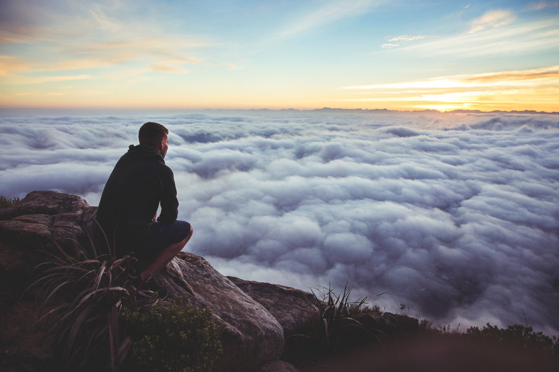 Man watching sunrise from a cliff top overlooking mist
