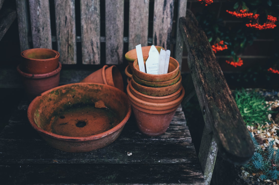 Empty garden pots in piles on a rustic outdoor chair