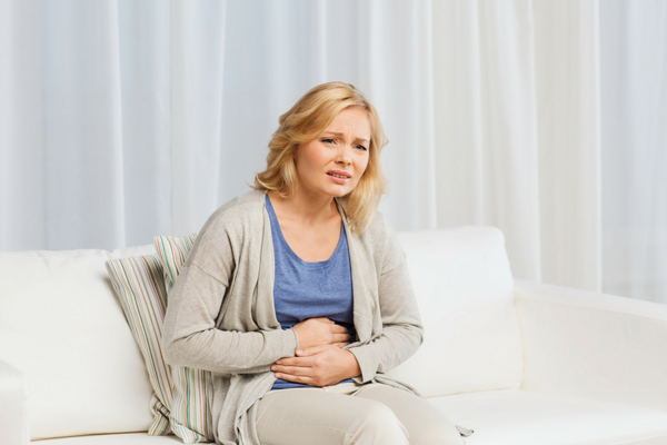 Woman sitting on couch holding stomach in pain