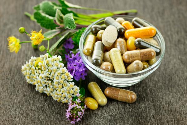 Bowl of herbal medicines and antibiotics next to fresh medicinal herbs