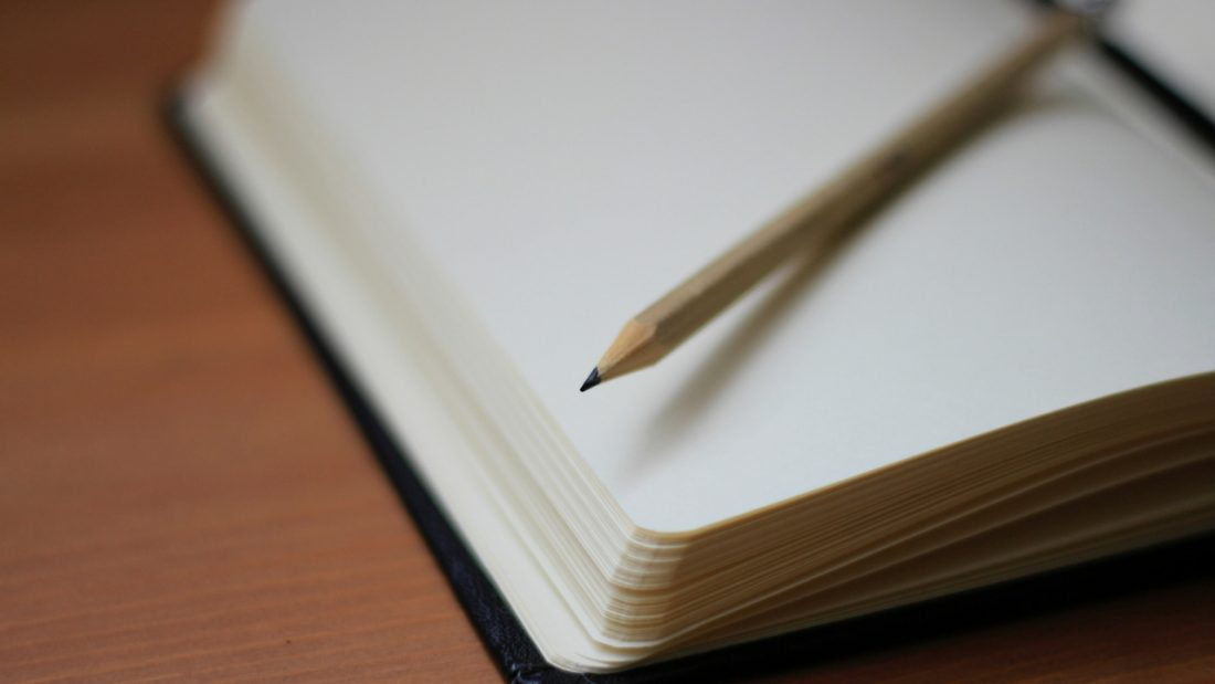 Open journal with a pencil