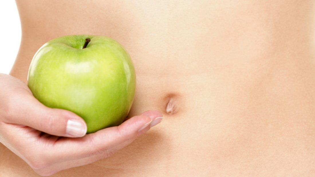 Woman holding a green apple in front of her stomach