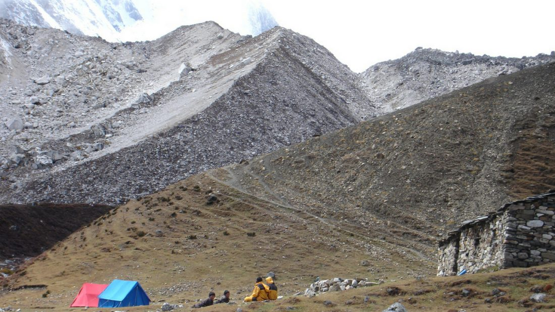 Snow covered moraine and stone house at Dharamasala Base Camp