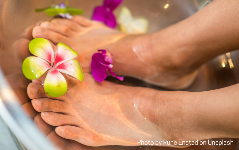 Feet soaking in a foot bath with flowers