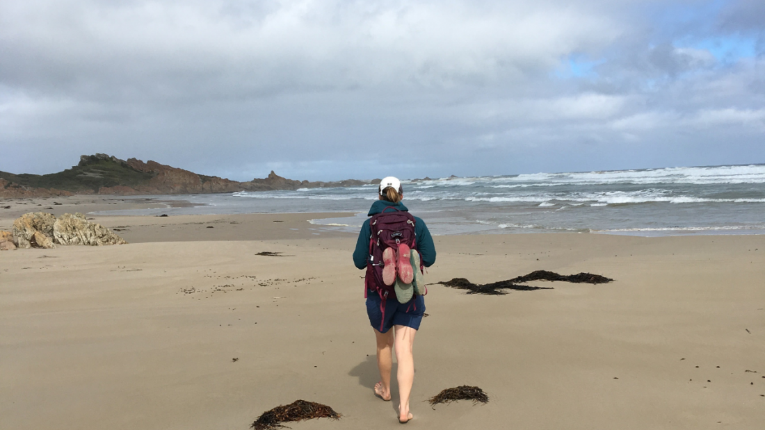 Sallyanne walking with her back pack along a beach in NW Tasmania