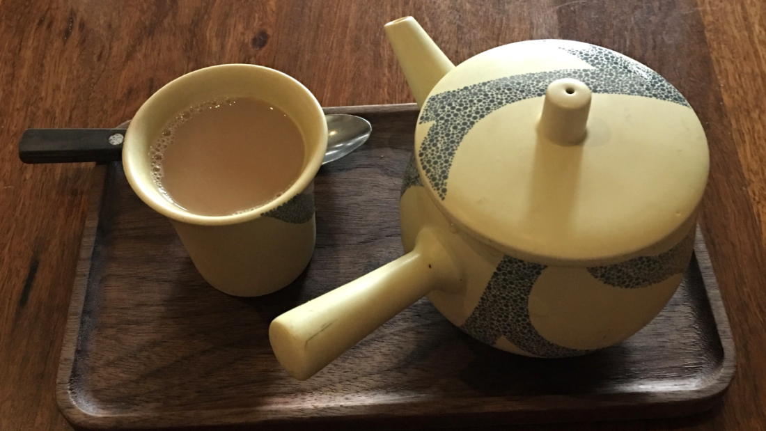 Teapot alongside a cup of masala chai