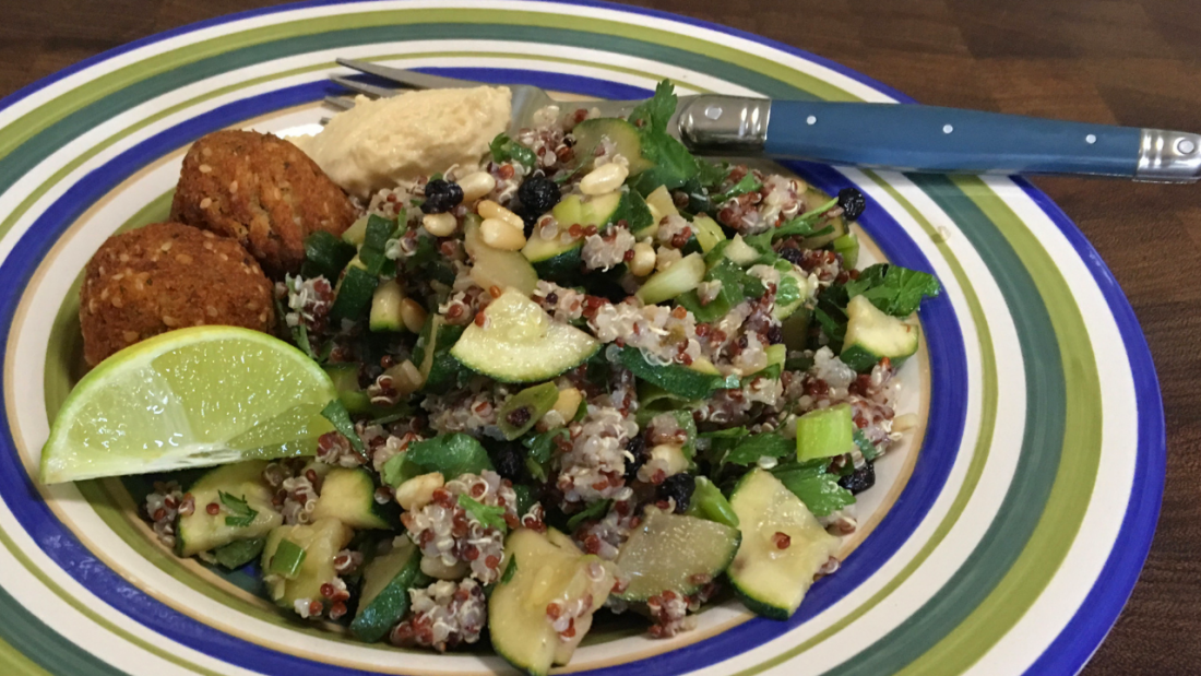 Dinner plate with quinoa and zucchini salad, lime, falafel and hummus