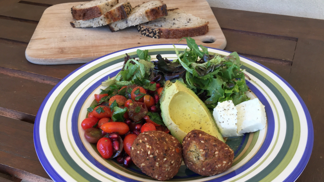 Plate of falafel, green leafy salad and whole grain sourdough bread
