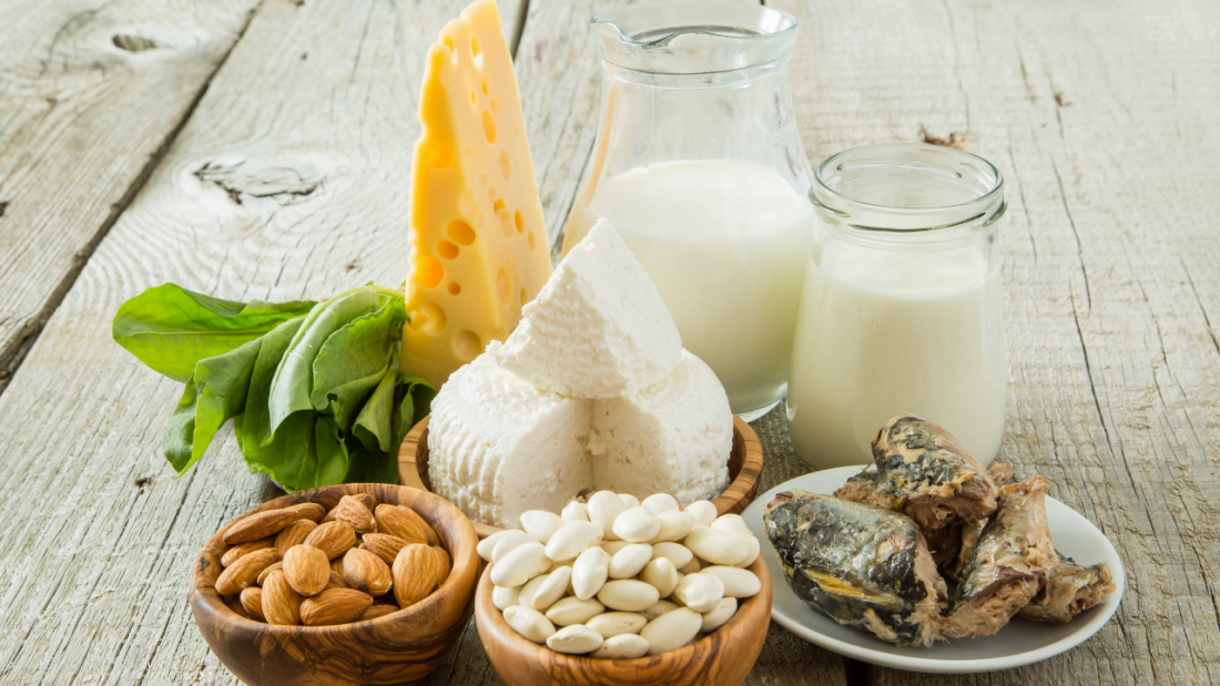 Display of calcium-rich foods on a table including almonds, leafy greens, legumes, cheese, milk and cooked salmon