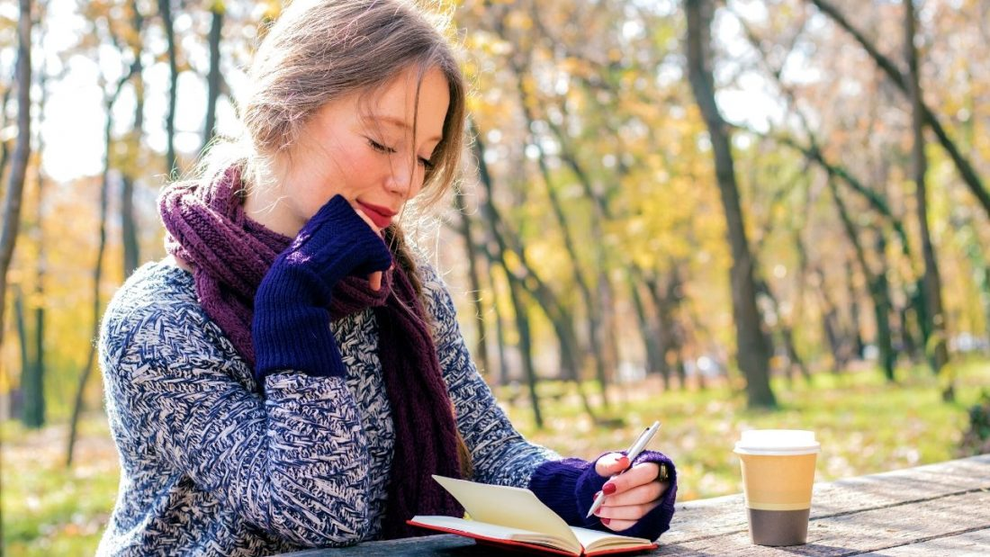Lady completing a mindful eating journal at an outdoor bench