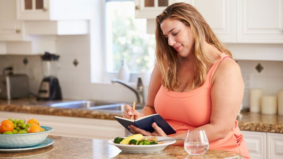 Lady completing mindful eating journal in the kitchen