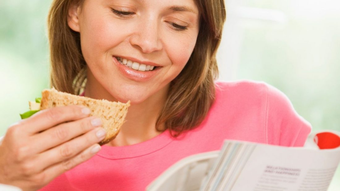 Woman eating a sandwich and reading at the same time