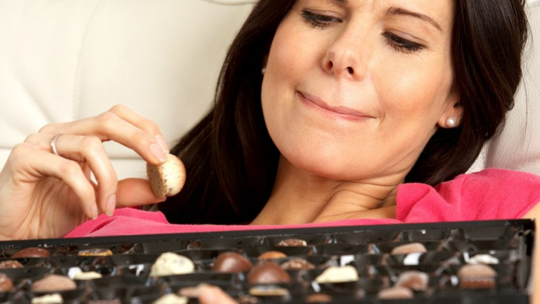 Lady choosing chocolates from a chocolate box but not sure whether to keep eating.