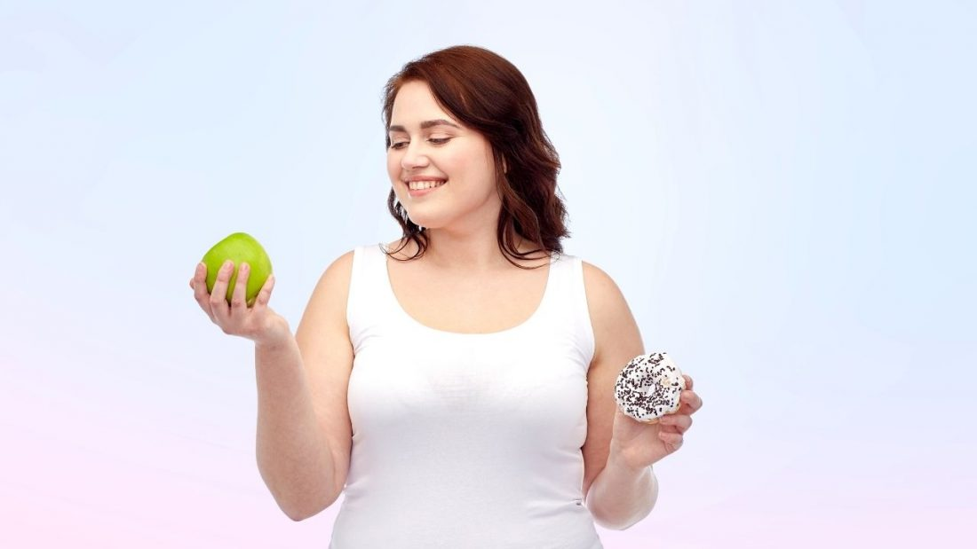 Lady holding an apple and a donut food rules inform the choices we make