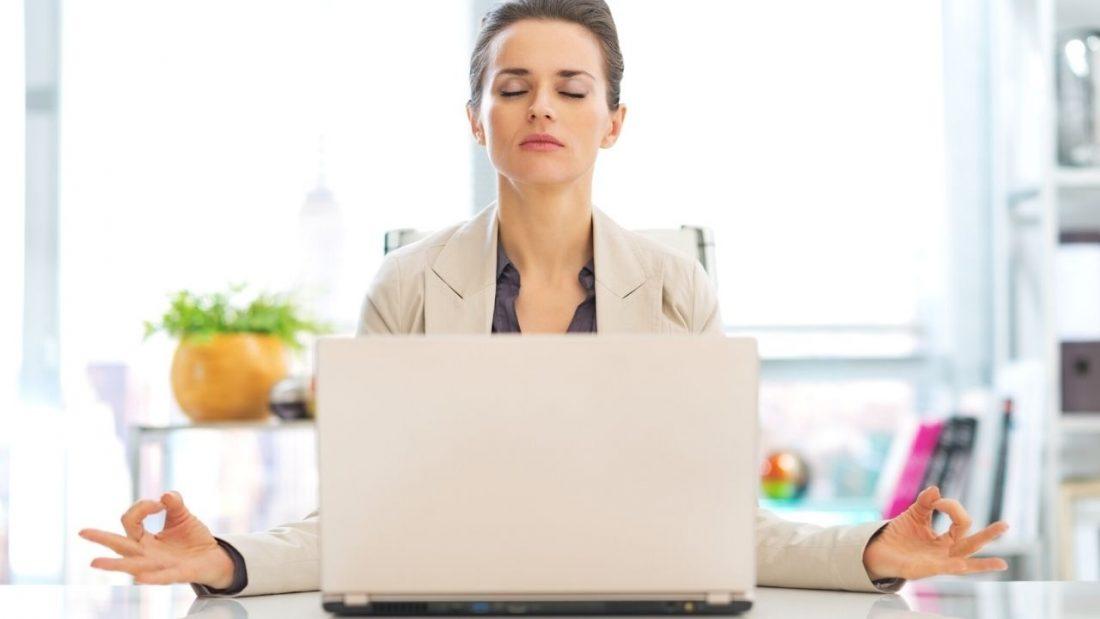 Lady sitting at work desk meditating