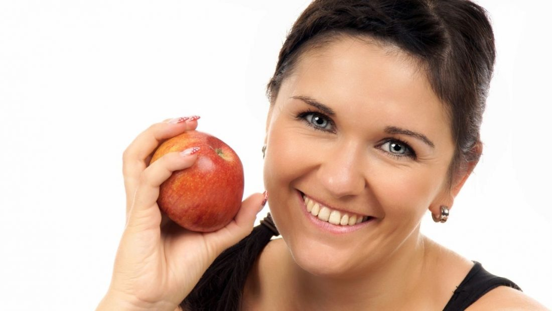 Lady smiling and holding a red apple