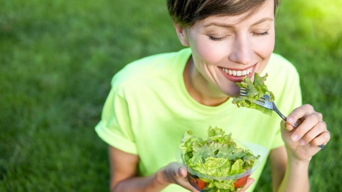Lady eating a bowl of salad outdoors