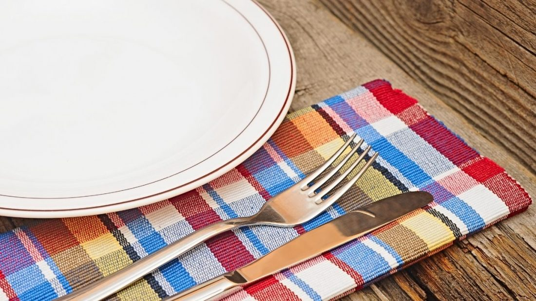 Empty white dinner plate, check napkin and knife and fork
