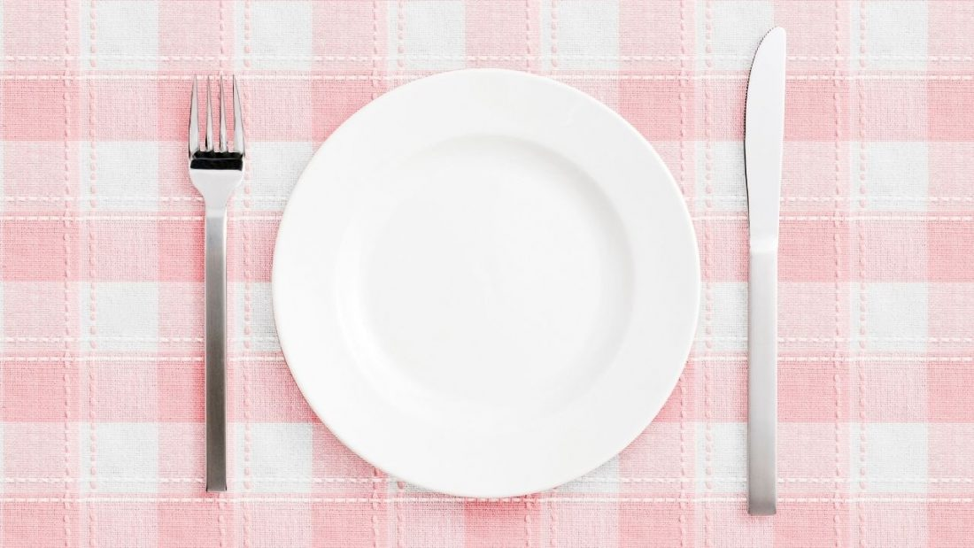 Empty white plate with fork and knife on a pink and white check table cloth