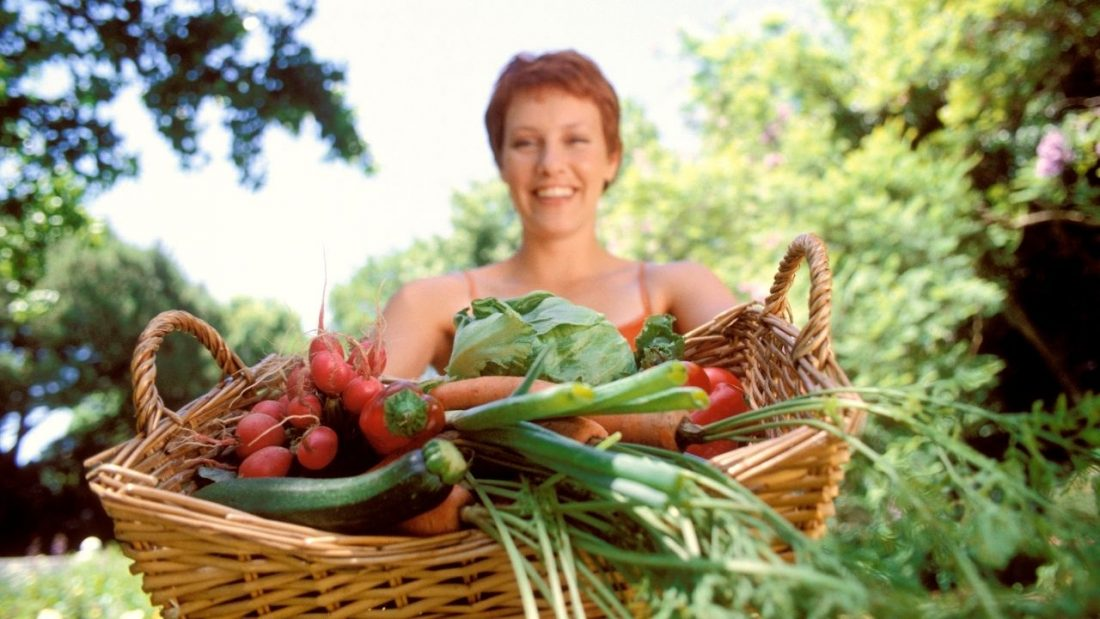 Woman holding can basket full of vegetables