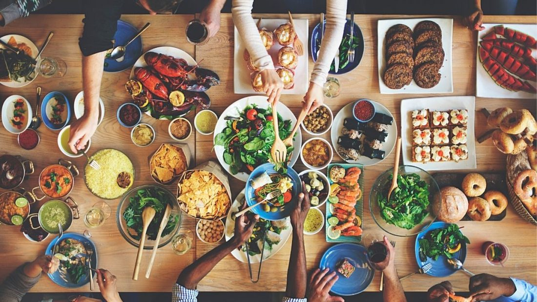Arial view of people selecting from a variety foods on large wooden table