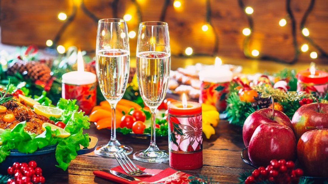 Two glasses of bubbly on a dining table decorated with candles and festive season food
