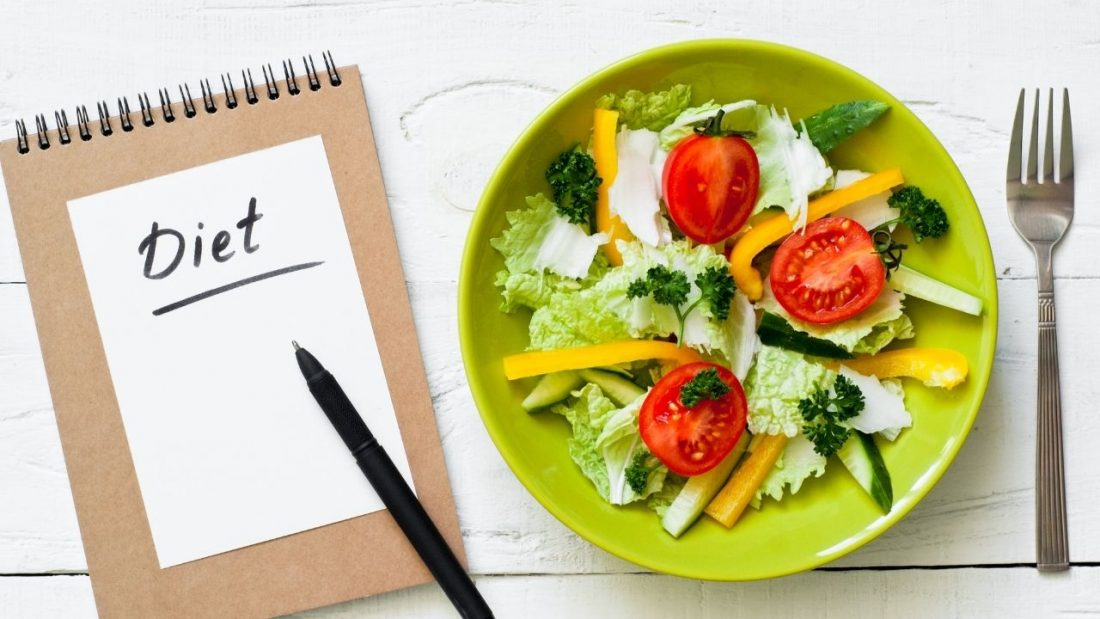 Diet notebook next to a plate of salad