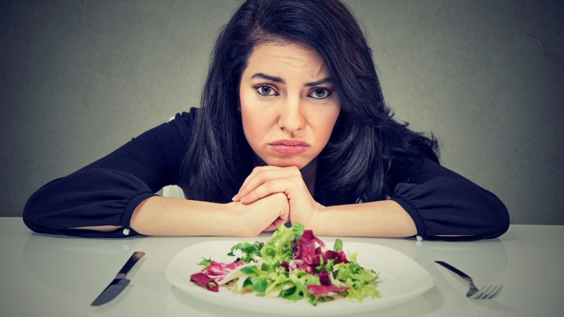 Woman looking very unhappy with her plate of salad