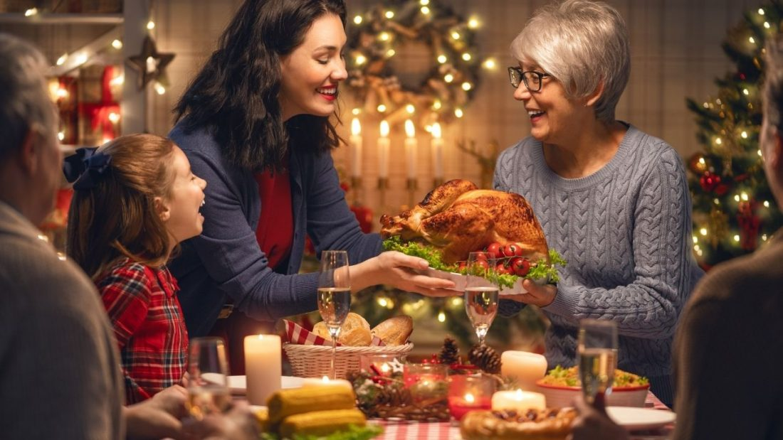 Christmas dinner and two women passing the plate of turkey