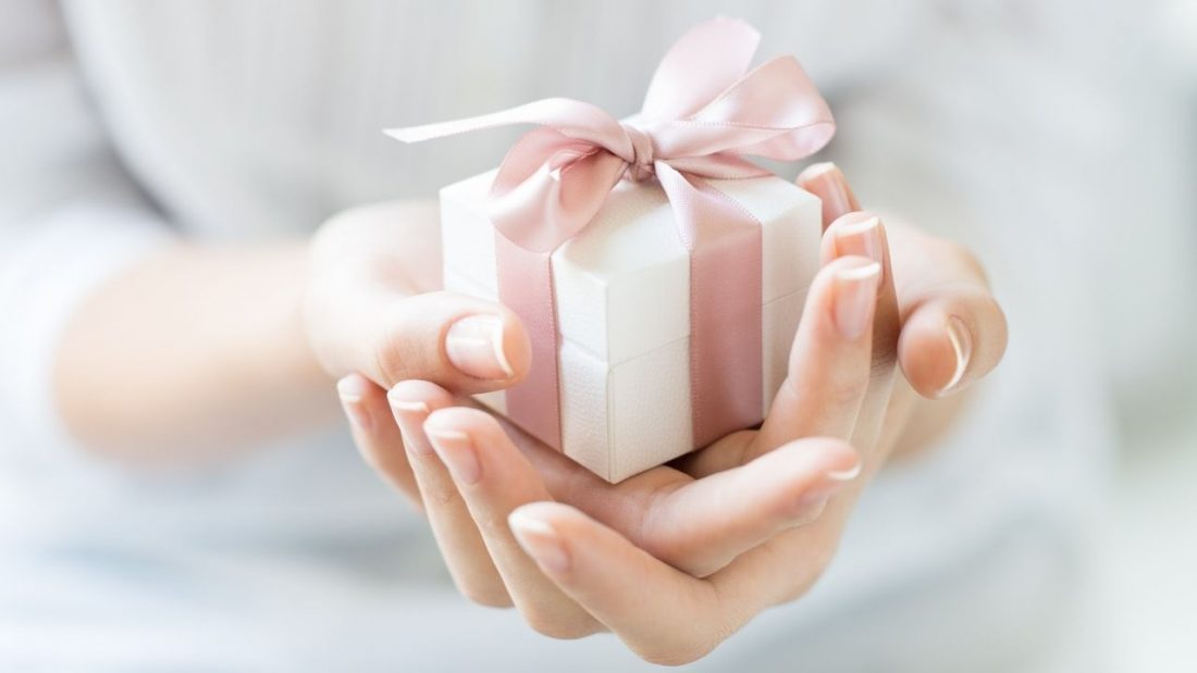 Lady holding a white gift wrapped in pink ribbon in her hands